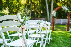 freie Trauung mit weißen Stühlen und Traubogen und Blumenschmuck