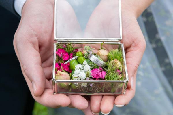 Traurunge in einer mit Blüten gefüllten Schachtel auf den Händen des Brautpaares